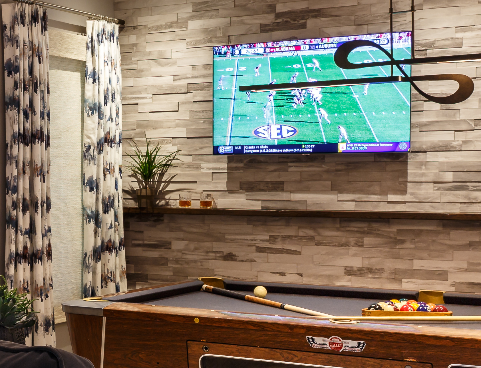 Stone wall behind pool floating shelf light fixture over pool table